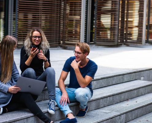 Trois jeunes assis sur des marches. Photographie de Buro Millennial